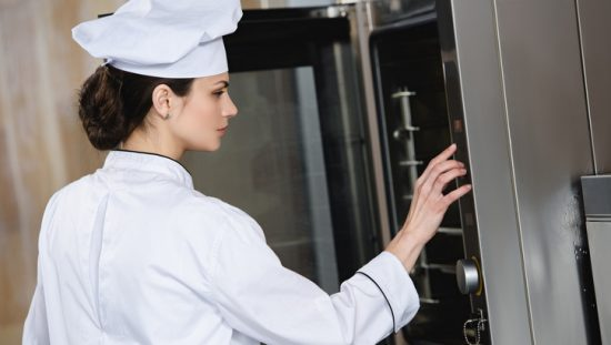 Chef setting an oven that follows NFPA 86-2019