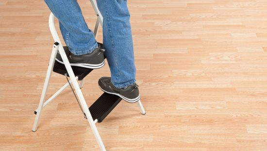 Two feet finding their way up a stepladder by safely following the ANSI ASC A14.11-2018 standard on a wooden floor