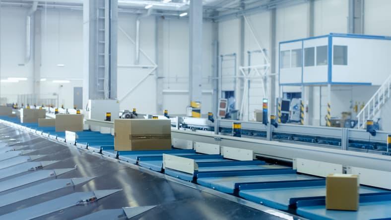 Blue conveyor shuttling boxes and kept safe thanks to ASME B20.1-2018