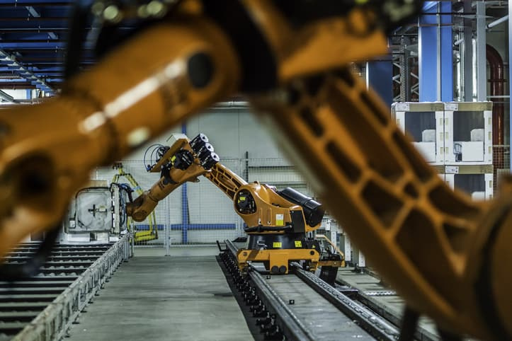 Orange robot arms follow ANSI/RIA R15.06-2012 in a factory to keep nearby humans safe.