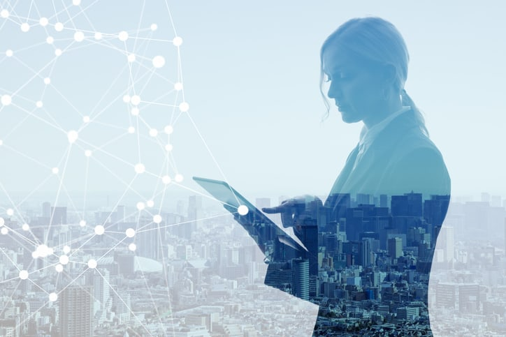 A woman is on a tablet, with a skyline of a city in the background to represent the need to protect personally identifiable information as specified in ISO/IEC 27018.