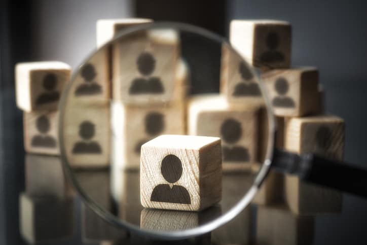 Stacked wooden blocks with an icon representing a person on them. One block is brought into view with a magnifying glass which represents protecting personally identifiable information as specified in ISO/IEC 27018.