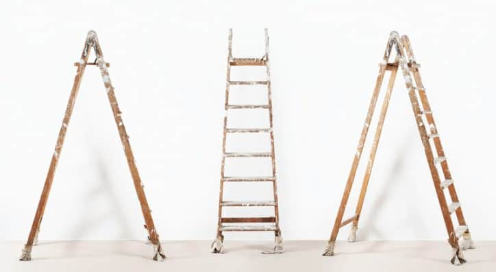 Three wooden ladders that are old and ready to be disposed of properly under ANSI standards.