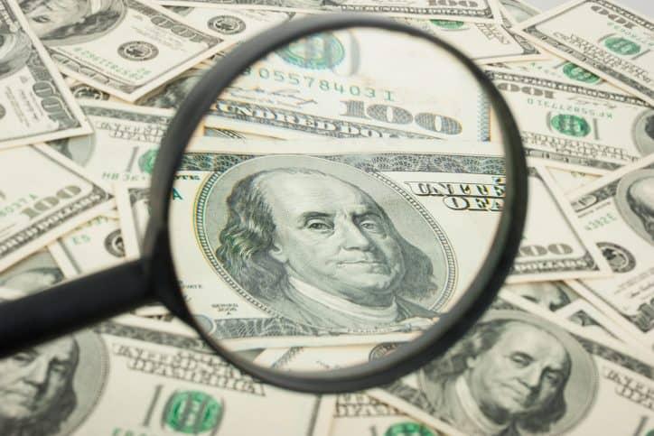 Magnifying glass looking at hundred dollar bills