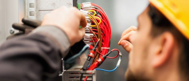 Worker performing maintenance testing specifications of red wires