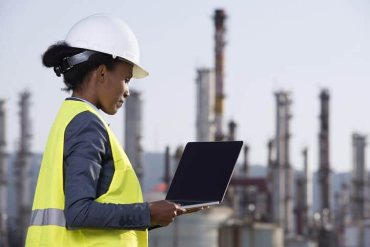Energy Engineer wearing work helmet and reflective vest, checking data of the refineries, using a tablet computer.
