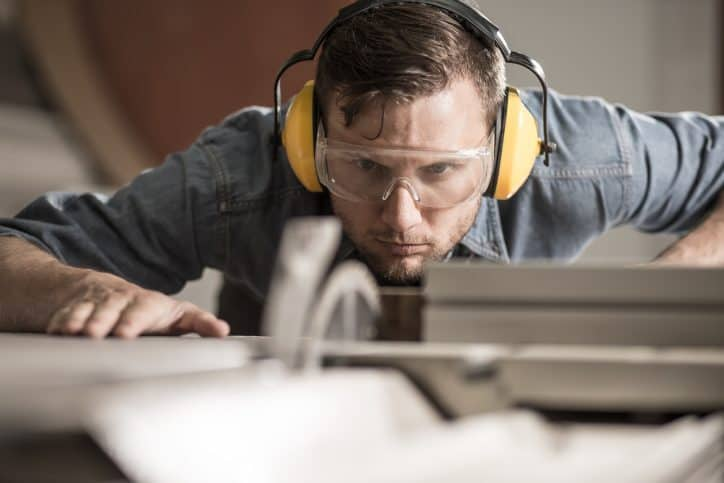 Man uses saw with hearing protection that meets ANSI/ASA S12.6-2008 requirements