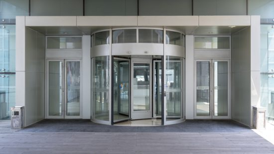 A building's revolving doors that follow ANSI/BHMA A156.27-2019