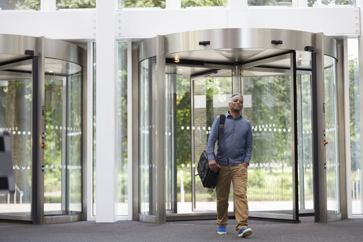 A man walking out of a revolving door that follows ANSI/BHMA A156.27-2019