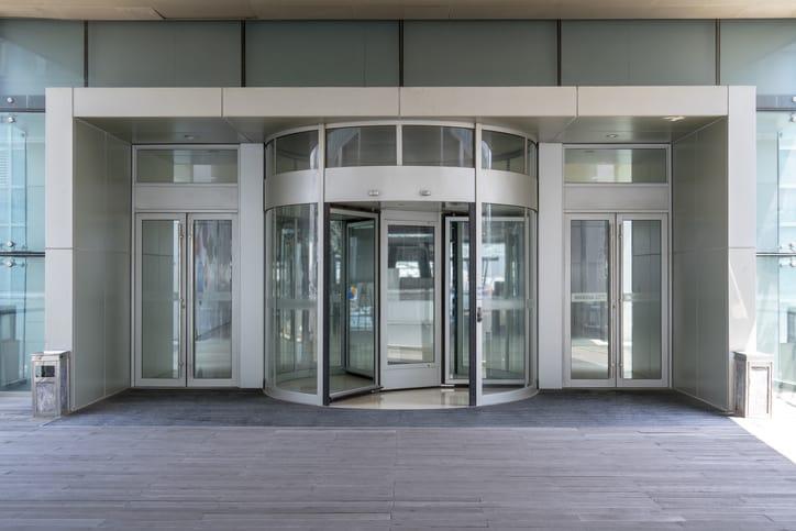 A building's revolving doors that follow ANSI/BHMA A156.27-2019