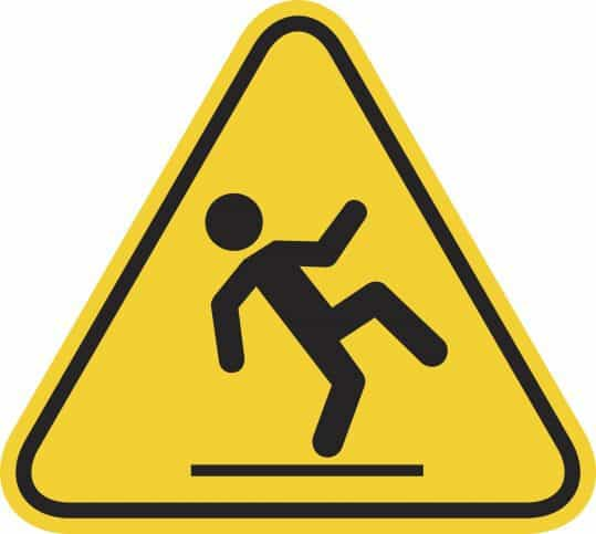 Slipping on yellow floor caution sign warns workers in tandem with ANSI/ASSE Z359 requirements.