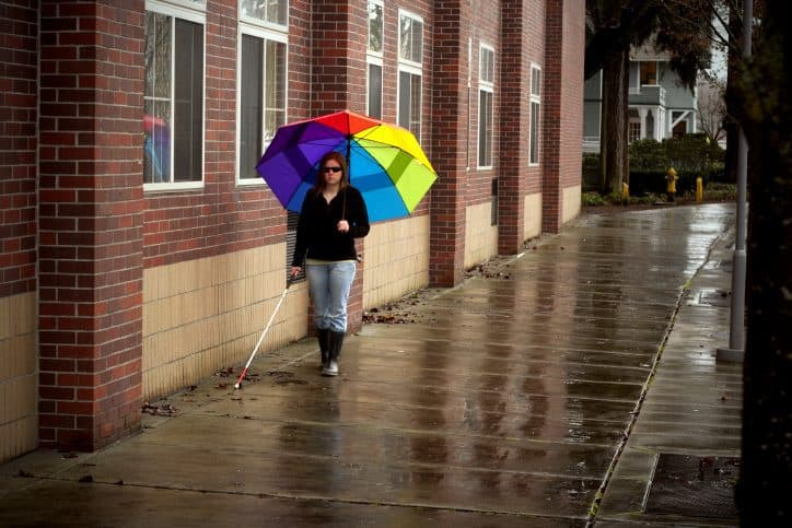 This blind woman walking in the rain with a rainbow umbrella is one of the people ADA standards are designed to help