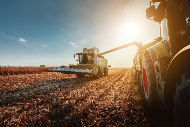 Heavy machinery that meet OPEI standards harvesting crops in a field