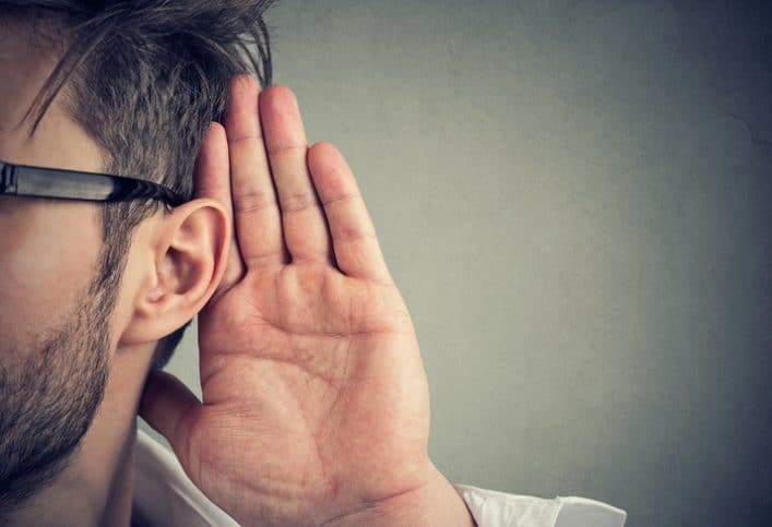 Middle aged man trying to evaluate room noise