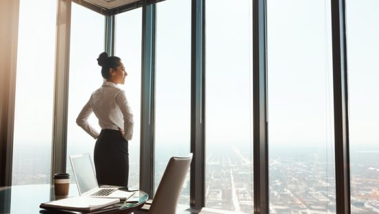 Businesswoman gazing out window, pleased to have completed an onsite visit and become ANSI/ISO/IEC 17024 accredited.