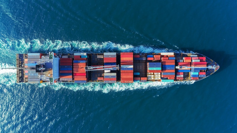 Barge crosses the sea with colorful shipping containers, since accreditation delivers confidence in the supply chain.