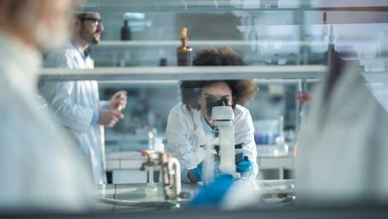 Woman in lab gazing into microscope while transitioning to ISO/IEC 17025:2017 management system requirements.