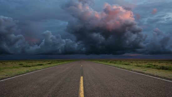 An empty road with a stormy sky that's representing trouble ahead and also ISO 22313:2020