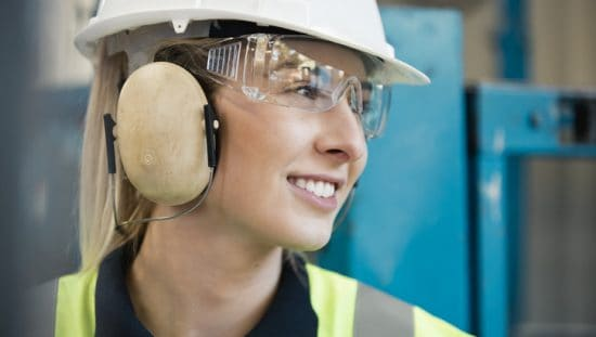 Happy woman wearing ANSI/ISEA Z87.1-2020 safety glasses to protect her face