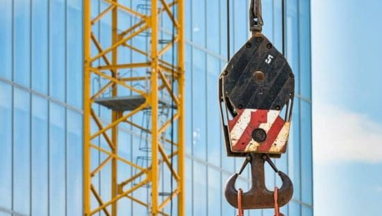 Red and white below-the-hook lifting device in construction site designed to ASME BTH-1-2017
