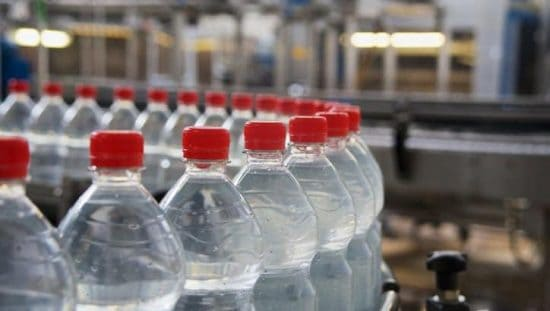 Plastic water bottles looping through factory conveyor belt marked to ISO 11469:2016