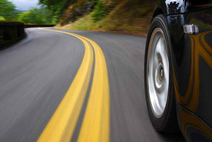 Black sports car speeds in landscape that blurs like a painting with wheels tested to SAE J 175-2020 for lateral impact