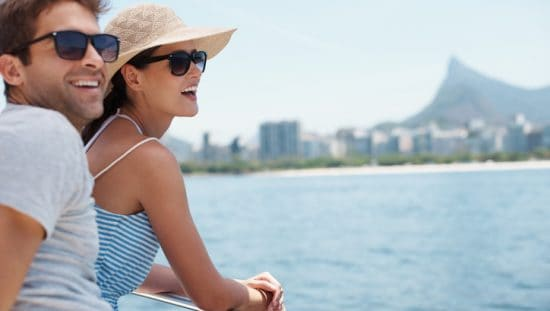 Happy couple wearing ANSI Z80 sunglasses on yacht