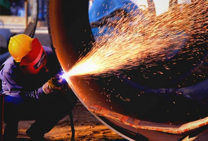 Welder shooting sparks while working on steel pipeline flanges with ANSI/MSS SP-44-2019