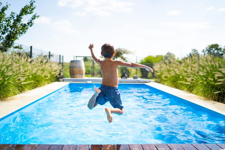Boy plunging into vacation swimming pool, crystalline blue and heated with an ANSI/ASHRAE 146-2020 pool heater.