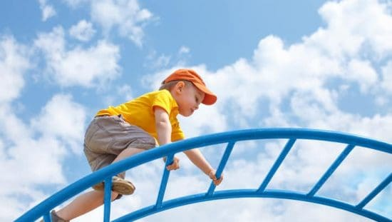 Boy climbing on blue monkey bars under cloudy sky assured to ASTM F1148-17 home playground safety specifications.