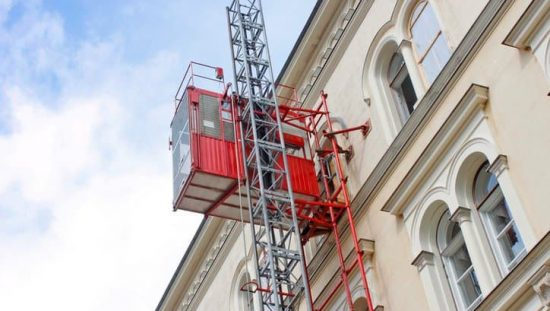 Hoist elevator on the side of a building while following ANSI/ASSE A10.4-2016