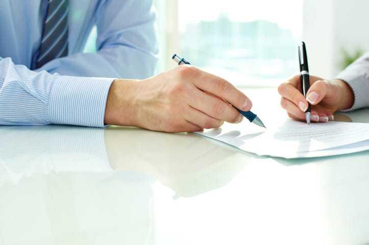Two hands writing standards documents and making changes via amendments, corrigenda, and errata.