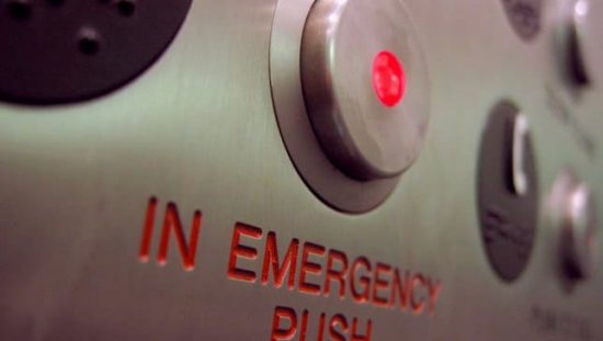 When in an emergency, light a stuck elevator, push the in emergency button, as covered by ASME A17.1.