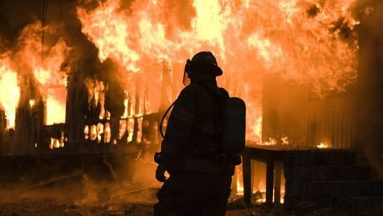 A professional firefighter staring into the face of a conflagration to meet the qualifications of NFPA 1001.