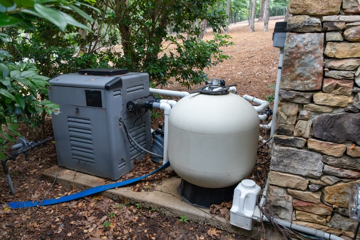 Pool heater pump, tested and rated to ANSI/ASHRAE 146-2020, next to a pool filter in a nice upper-class home.