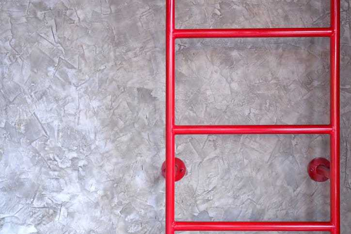 A bright red ladder in an industrial warehouse highlights the importance of safety ladders.