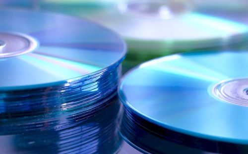 Piled blue CDs represent the ISO image disk format.