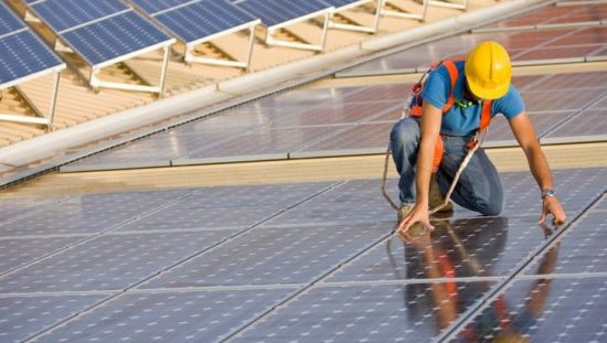 Worker in hardhat carefully installing solar photovoltaic (PV) panels that will undergo IEEE C57.159-2016 photovoltaic transformers.
