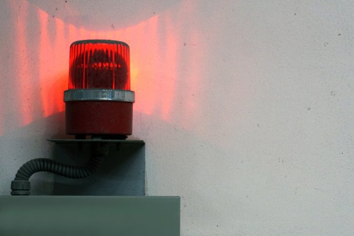 Bright red ANSI/ISA 18.2-2016 alarm system in action to prevent a factory accident.