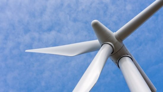 Wind turbine rotor spinning under blue cloudy sky and reachable by an ASME A17.8-2016 wind turbine service elevator.