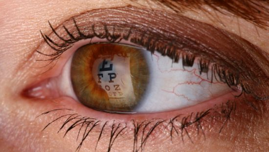 Brown iris during eye exam reflecting optotypes of Snellen chart designed to ANSI Z80.21-2020 to find her visual acuity.