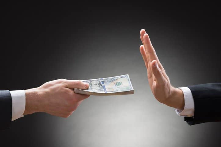 Businessman rejecting a heavy cash bribe after reading ISO 37001:2016 for anti-bribery management.