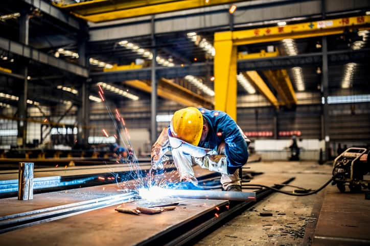 Welder geared up in large warehouse and keeping the difference between welding symbol and weld symbol in mind.