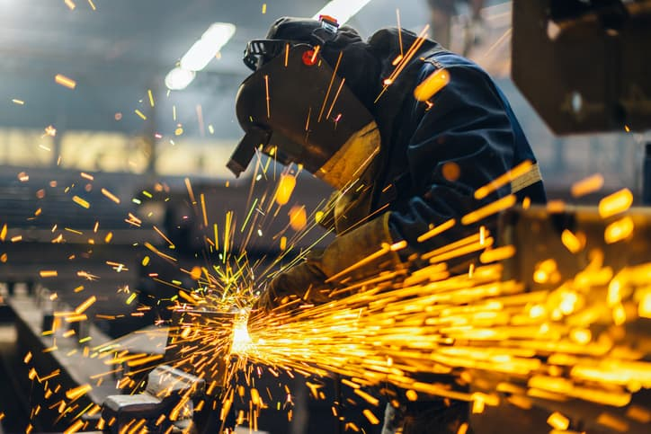 Welder letter sparks fly with a grinder while following the AWS A3.0:2020 standard welding terms.
