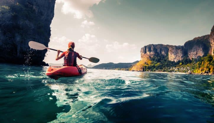 Woman entering the high seas and taking part in ISO 21101 adventure tourism by kayaking over blue cliffside water.