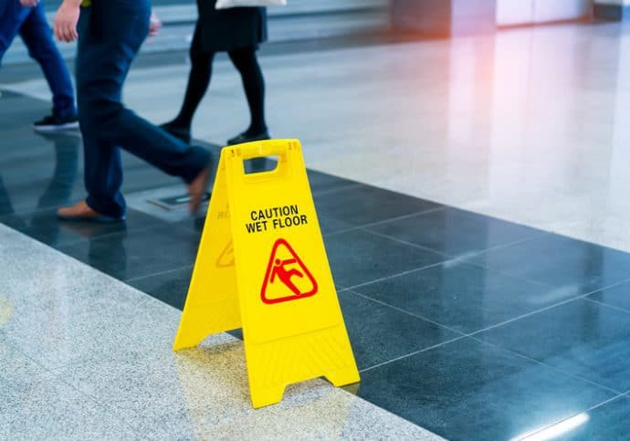 A bright yellow wet floor sign set before walking people on a walkway tested for NFSI B101.1-2020 wet SCOF.