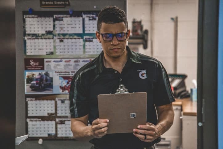 Man checking out his warehouse safety checklist to make sure his workplace is safe from hazards.