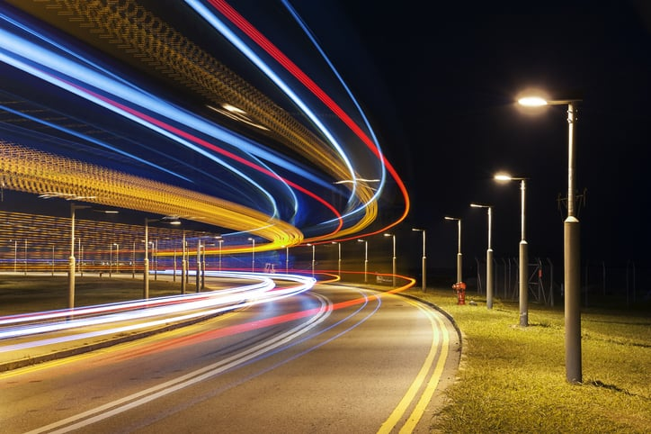 Cars pass by in streaming colors beside roadway lighting marked to ANSI C136.15-2020 luminaire identification.