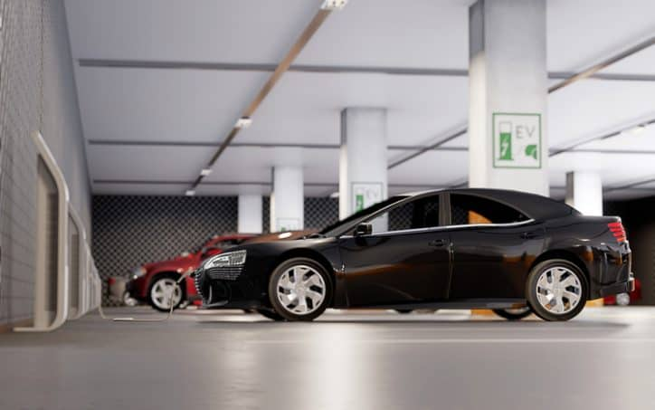 Electric vehicles charging to AC charging system infrastructure standards in parking garage.