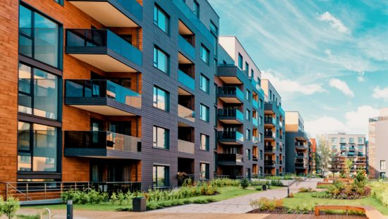 A multifamily building with verdant greenery assured to safety with ANSI/AARST MAMF-2017 radon measurements.